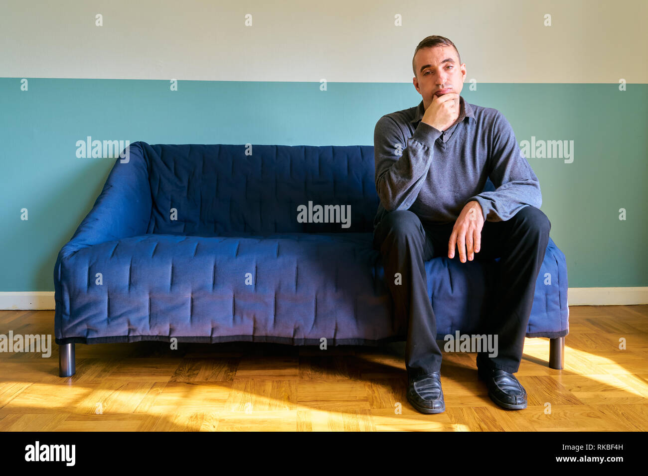 Handsome guy posing - serious expression and thinking about something sitting on the sofa - Stock Image