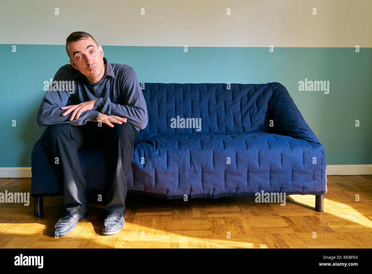 Handsome guy posing - lazy man sitting on the sofa - Stock Image