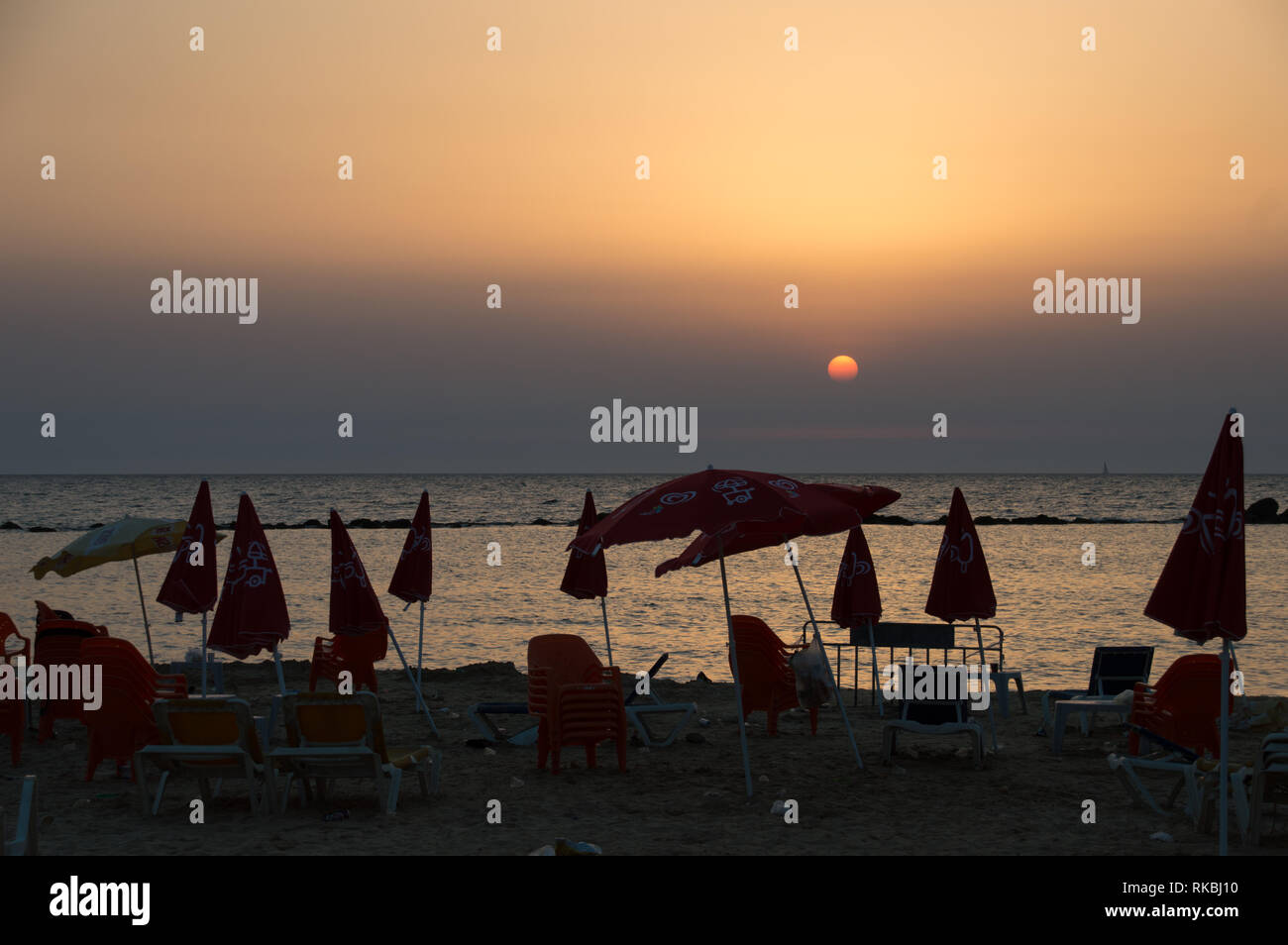 Warm summer sunset view of an urban dirty beach, full of garbage on the sand, chairs and umbrellas, some open, some closed, in red, seascape. - Stock Image