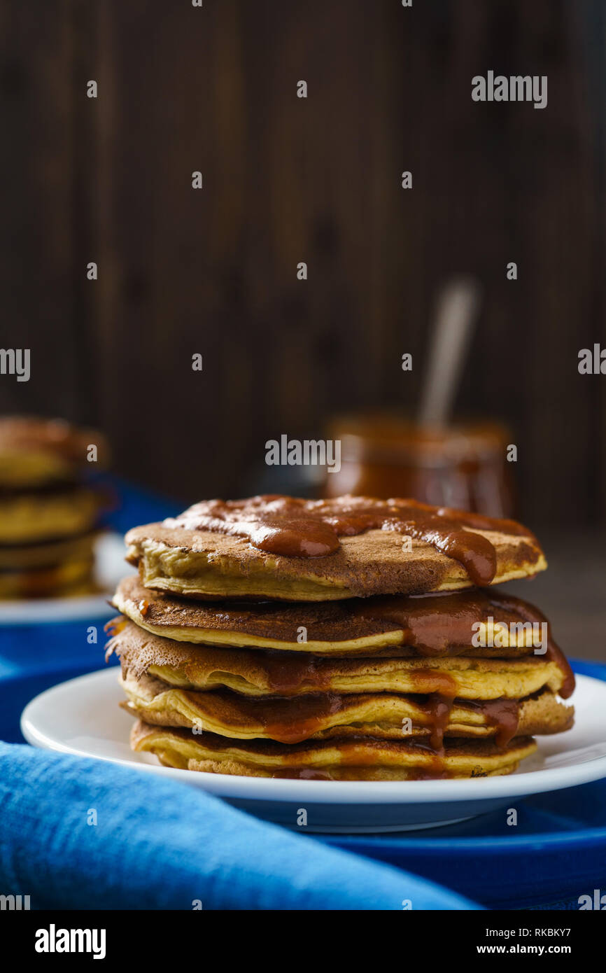 Pumpkin pancakes with caramel on wooden background Stock Photo