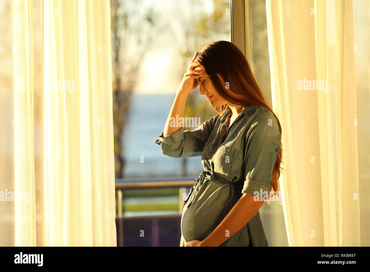 Side view portrait of a worried pregnant woman complaining at home Stock Photo