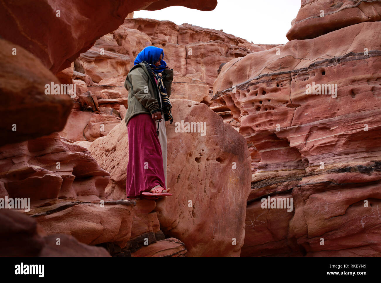 A Bedouin girl stands on rock formations in Egypt's Coloured Canyon, located near the Sinai town of Nuweiba, Egypt. (Photo/Hasan Jamali) - Stock Image