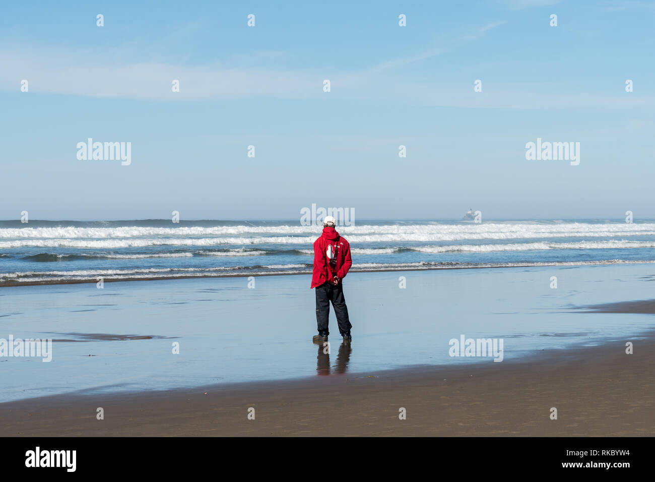 A member of Haystack Rock Awareness Programs with his signature red sweatshirt watches and observes the ocean - Stock Image