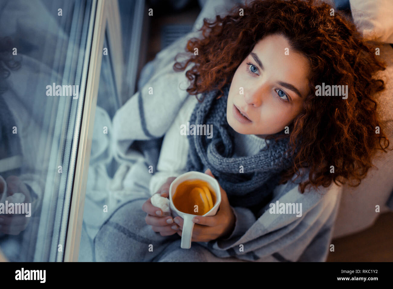 Curly woman wearing scarf suffering from sneezing and coughing - Stock Image