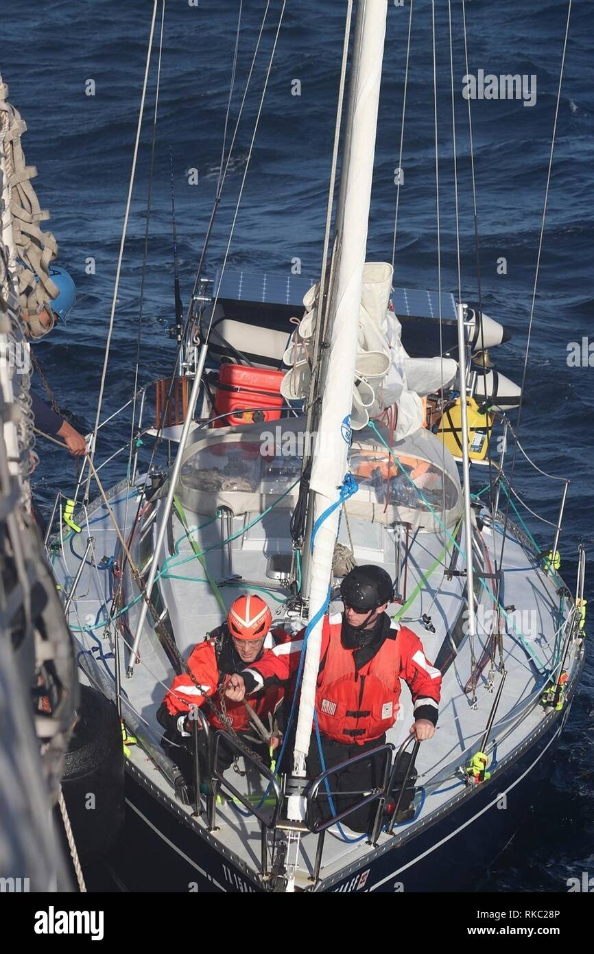 U.S. Coast Guard Cutter Reliance crew connects a tow line to the disabled sailboat C'est La Vie floundering in the Atlantic Ocean 110 miles off the coast of Virginia Beach February 8, 2019 near Virginia Beach, Virginia. The 32-foot sailboat snapped the tiller while traveling from Sheepshead Bay, New York, destined for St. Croix. Two sailors were rescued and the boat towed to safety. - Stock Image