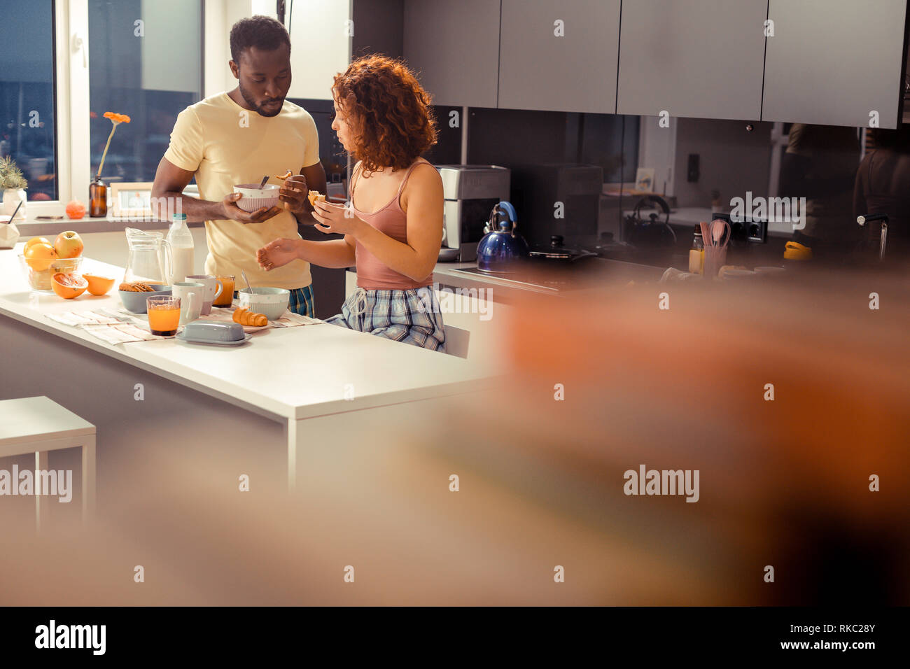 African-American husband sharing his cereals with his beloved - Stock Image