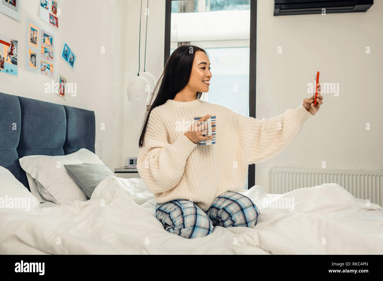 Dark-haired woman wearing comfy pink sweater making selfie - Stock Image