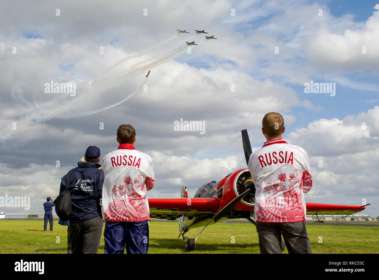 Russian pilots at the World Aerobatic Championships at Silverstone, UK, watching flying display. Sukhoi Su-26 aerobatic plane. Space for copy - Stock Image