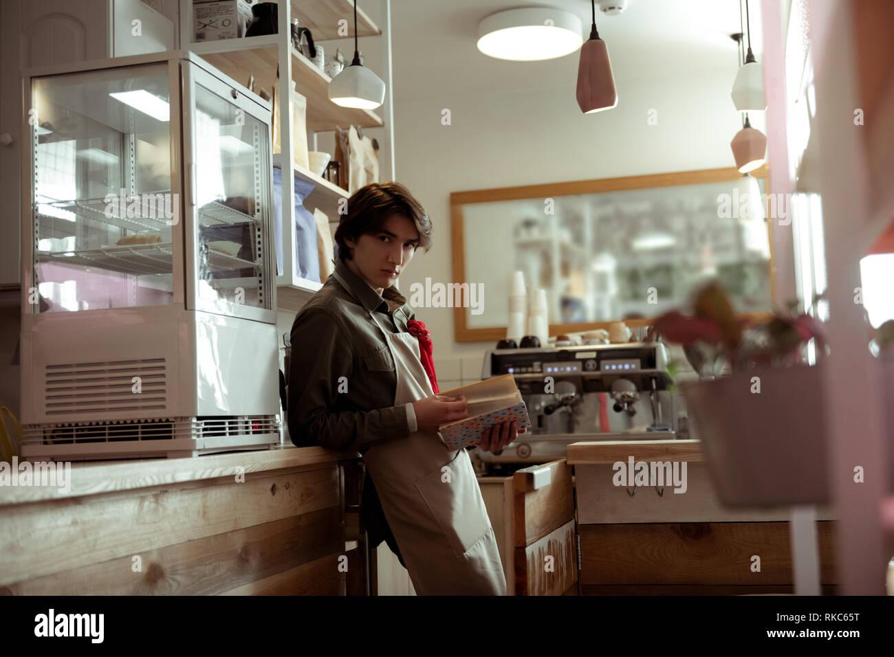 Concentrated good-looking man with heavy gaze having break in cafe - Stock Image