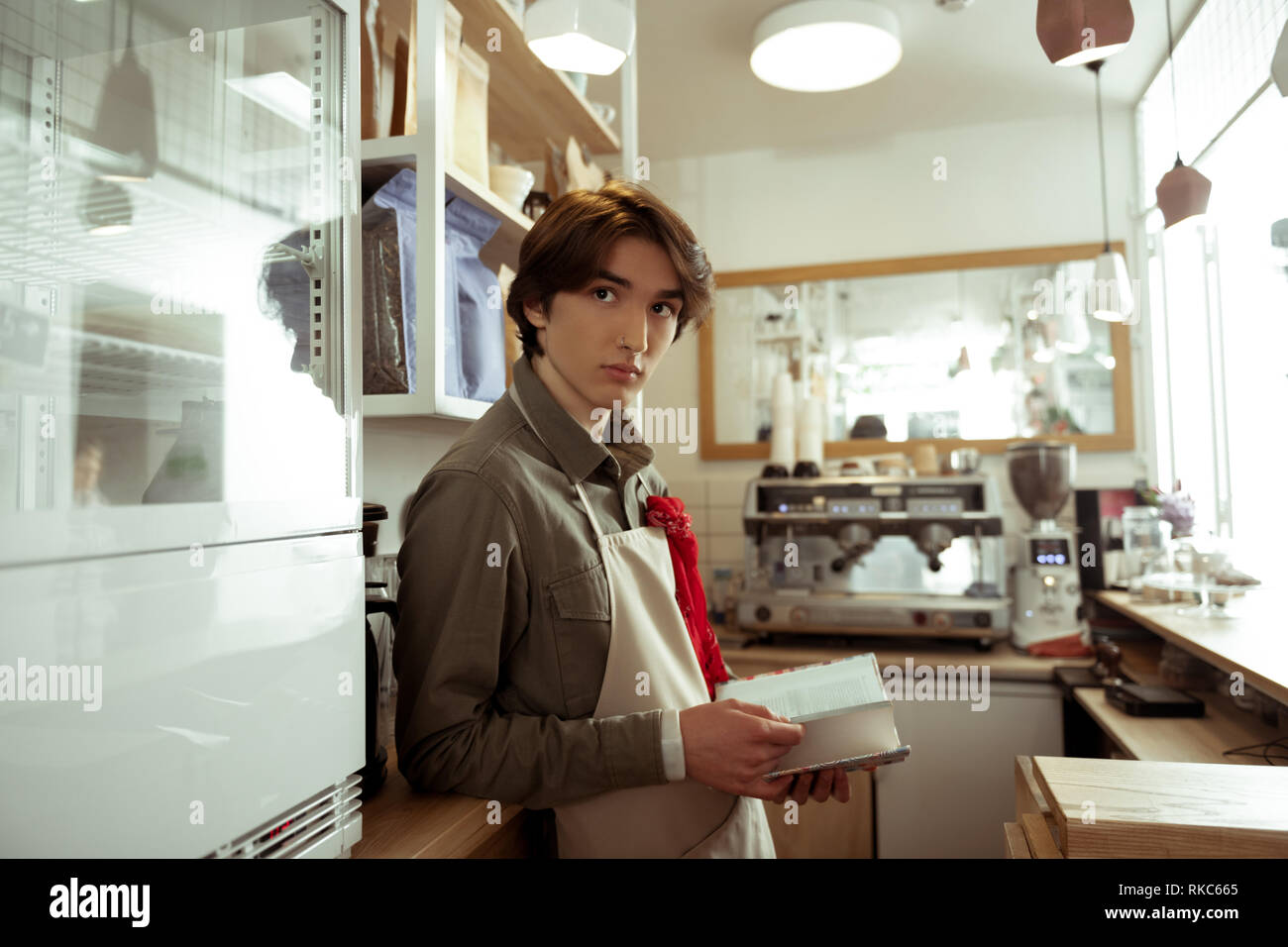 Dark-haired young barista with nose piercing flipping through book - Stock Image