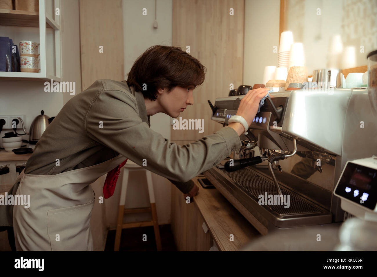 Dark-haired barista with nose piercing cleaning coffee equipment - Stock Image