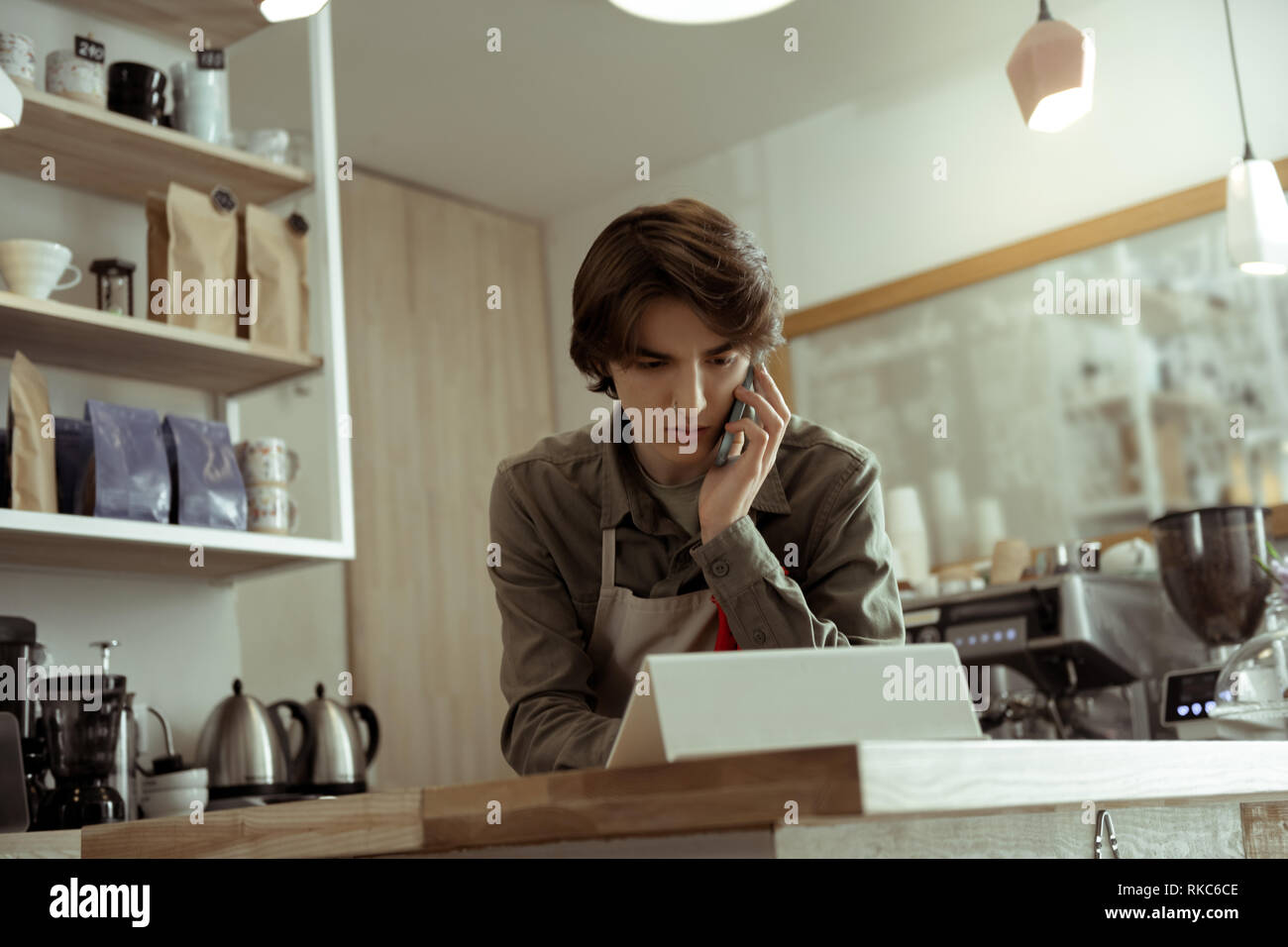 Attentive good-looking man discussing work moment on mobile phone - Stock Image