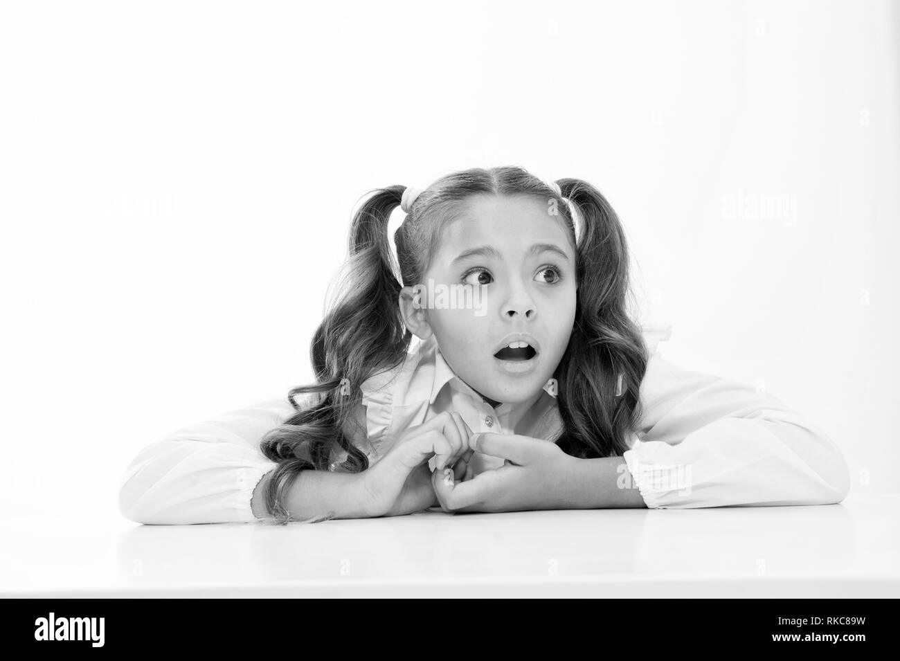 Pupil lean desk isolated white. Perfect schoolgirl tidy fancy hair. School as stranger environment. Prepare kid first school day. Schoolgirl stressful scared worrying face. Stressful event for her. - Stock Image