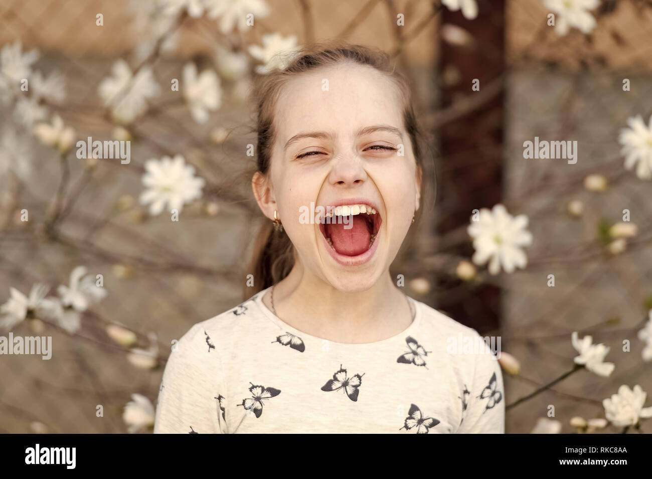 Child smile on floral blossom in spring. Child with fresh look and long hair. Stock Photo
