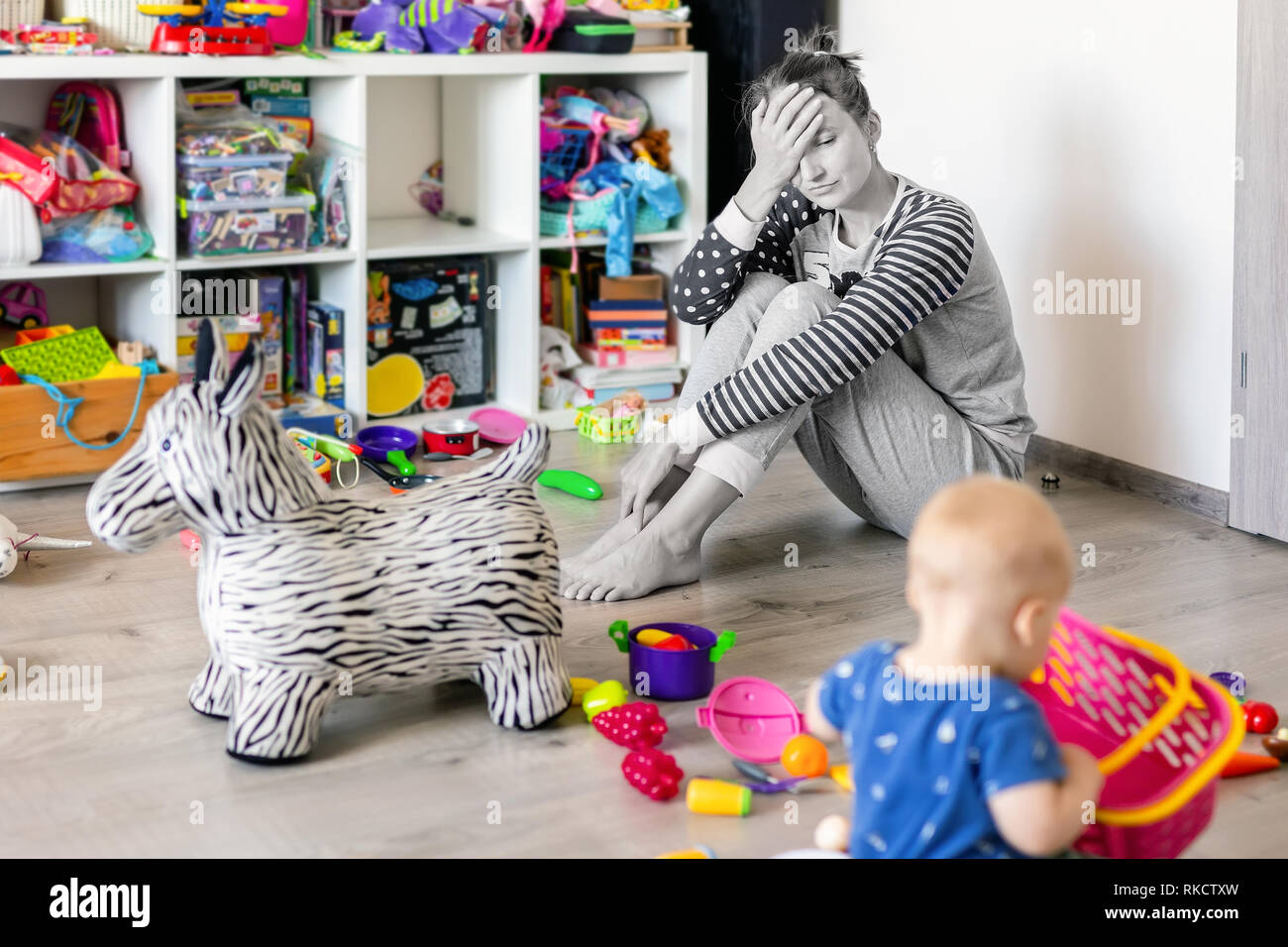 Tired of everyday household mother sitting on floor with hands on face. Kid playing in messy room. Scaterred toys and disorder. Happy parenting - Stock Image