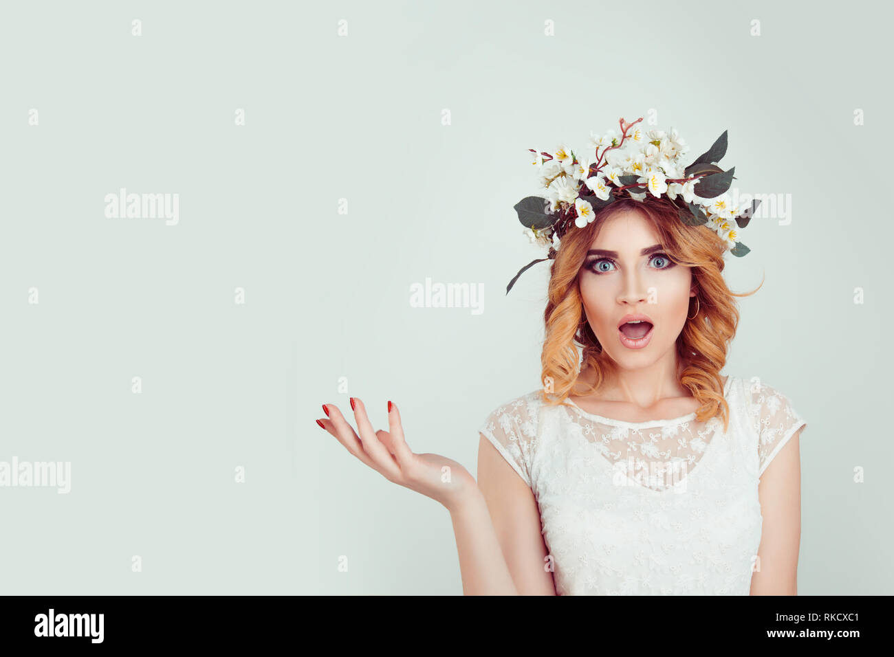 Surprised stunned woman in floral headband portrait - Stock Image