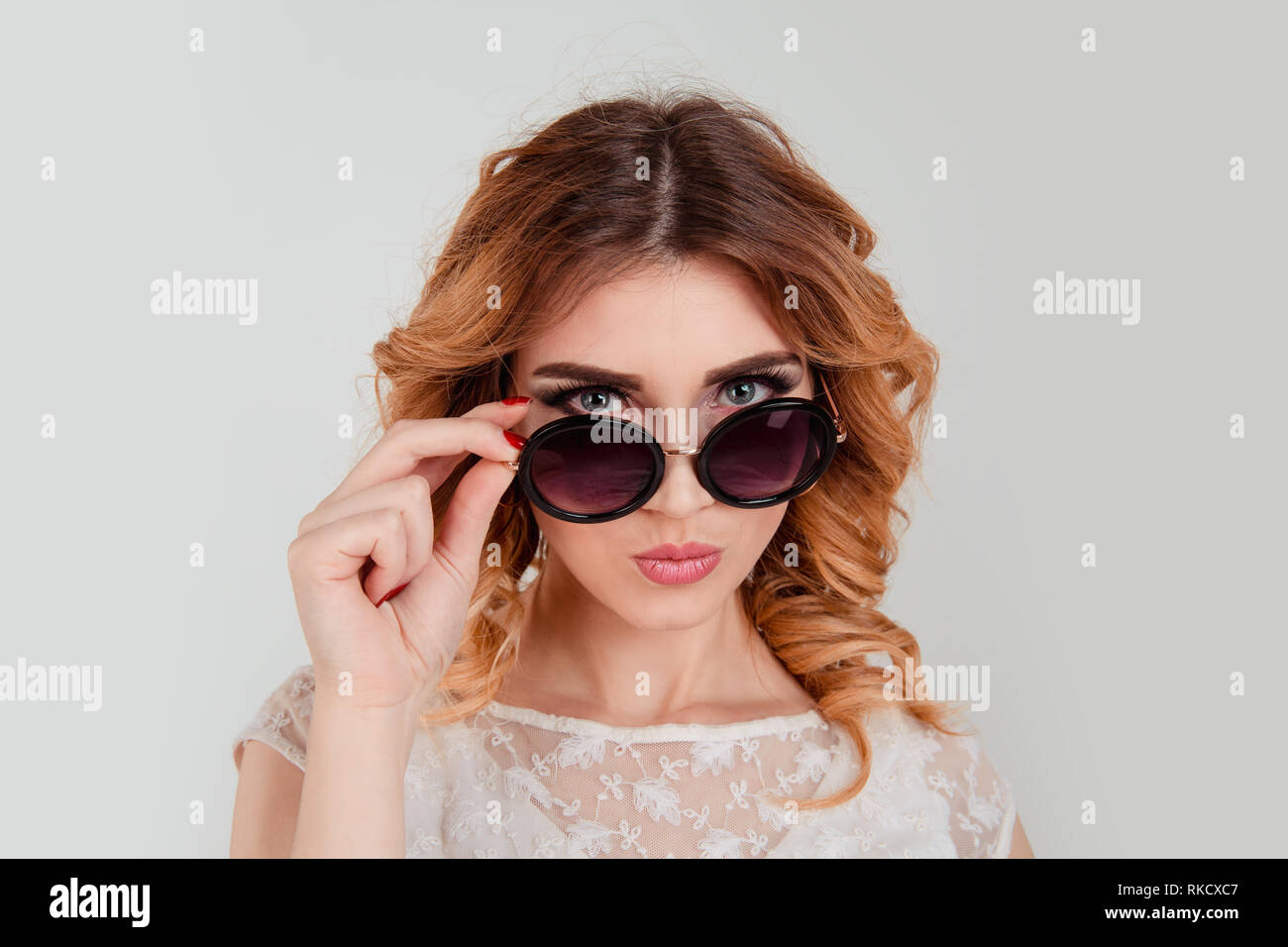 Skeptical woman hold sunglasses - Stock Image