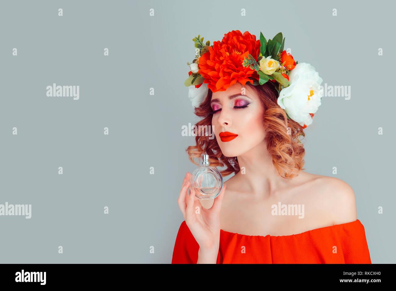 woman iwith peony headband smelling a perfume - Stock Image