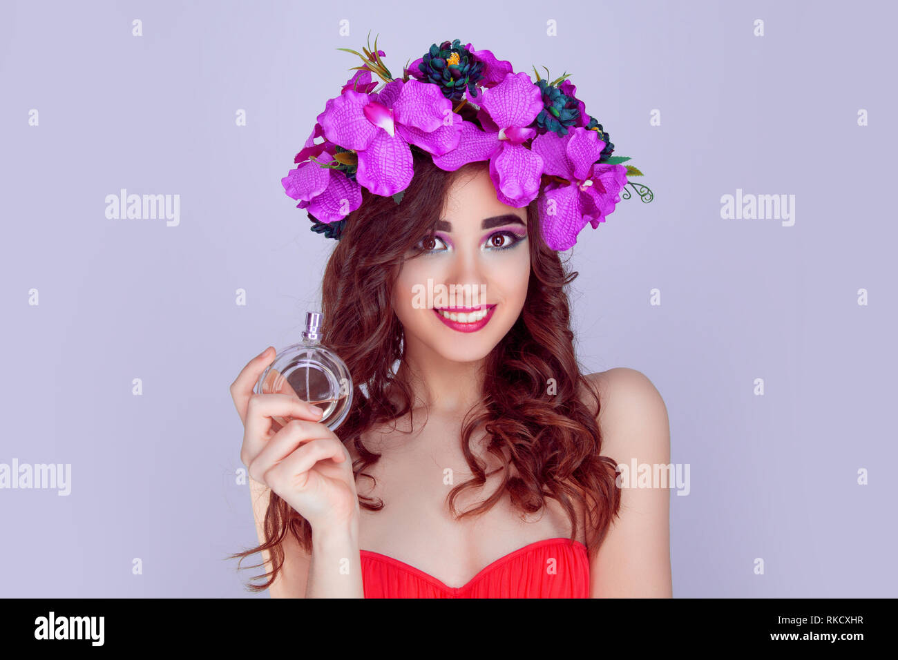 woman with floral crown giving perfume bottle - Stock Image