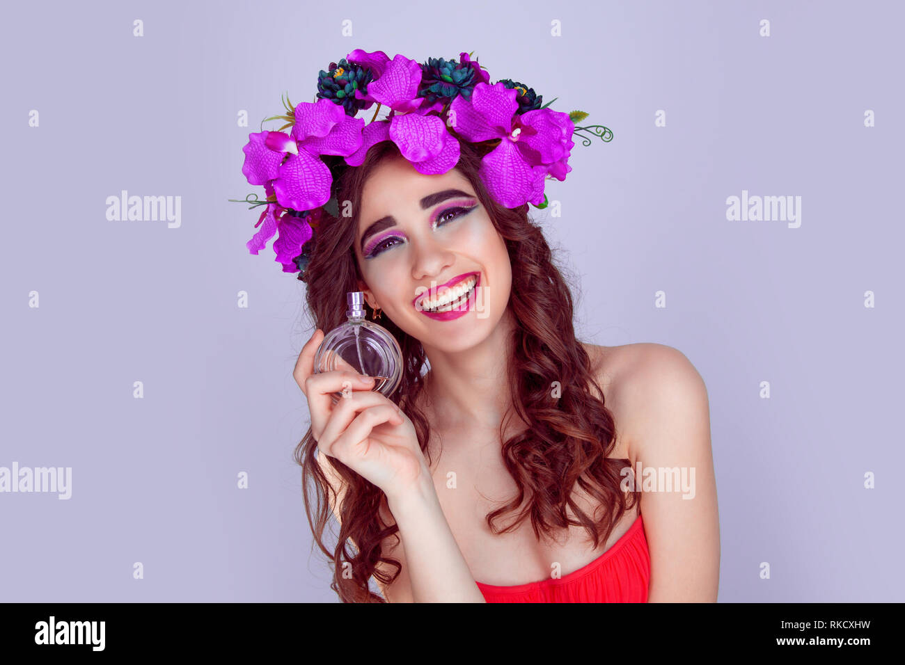 woman with floral crown holding perfume bottle laughing - Stock Image