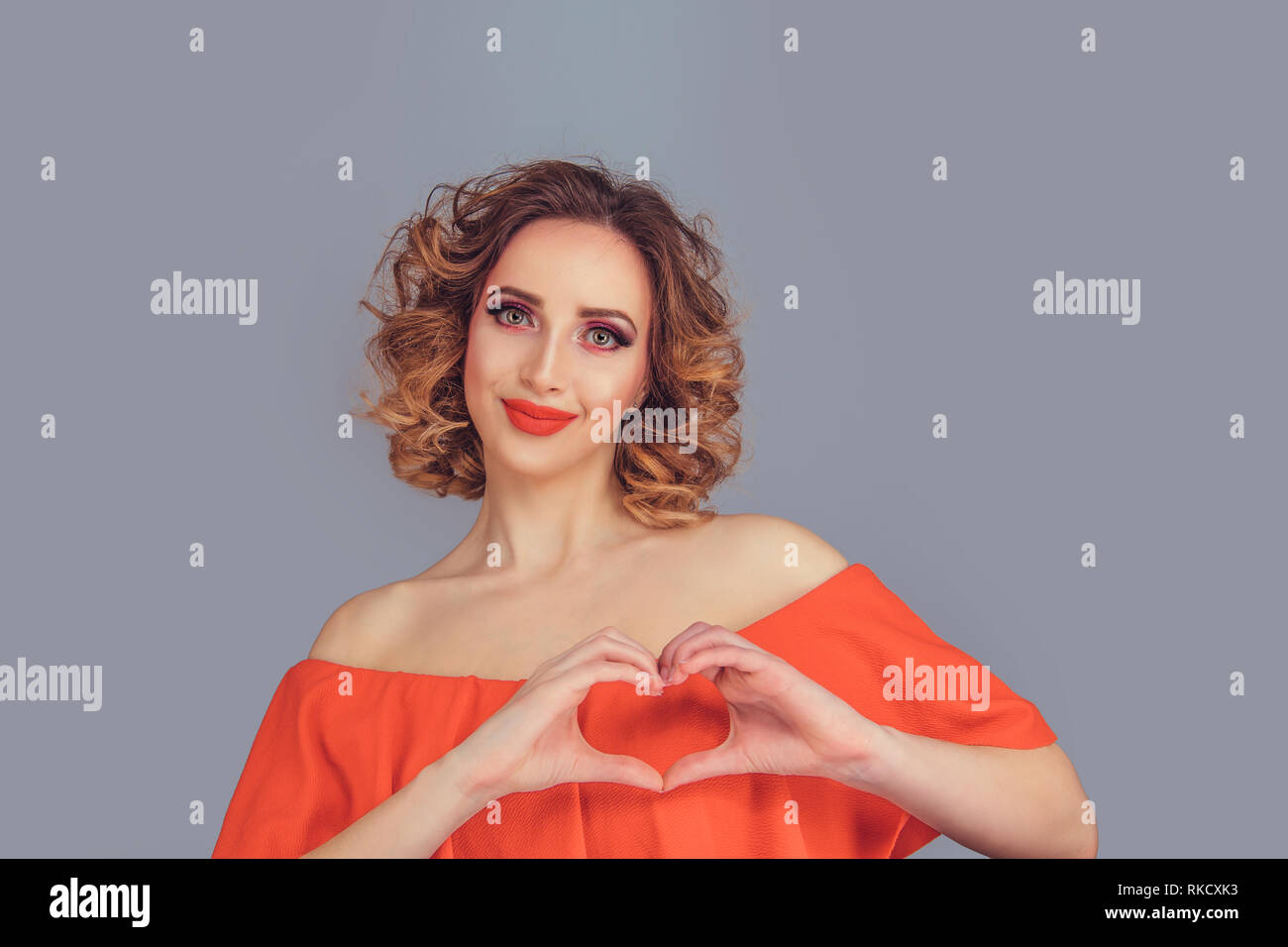 smiling happy young woman making heart sign with hands - Stock Image