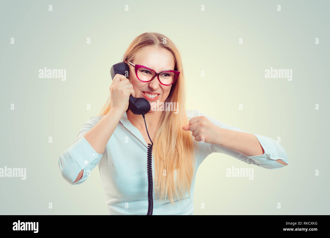 Furious woman speaking on phone - Stock Image