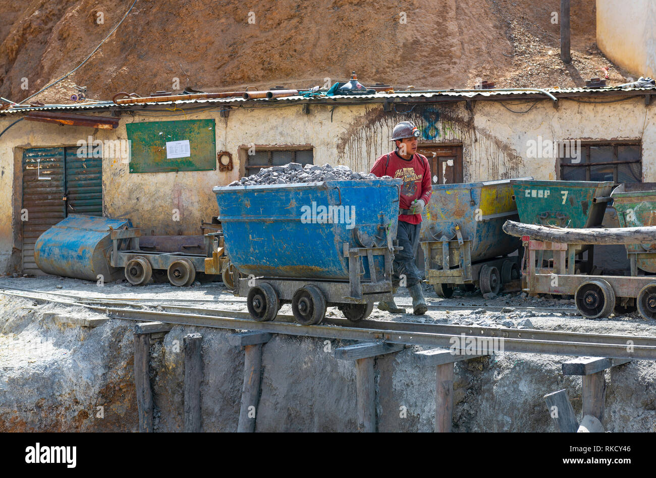 A bolivian miner with a carriage filled with rocks containing silver by a mine shaft of the Cerro Rico in the city of Potosi, Bolivia. - Stock Image