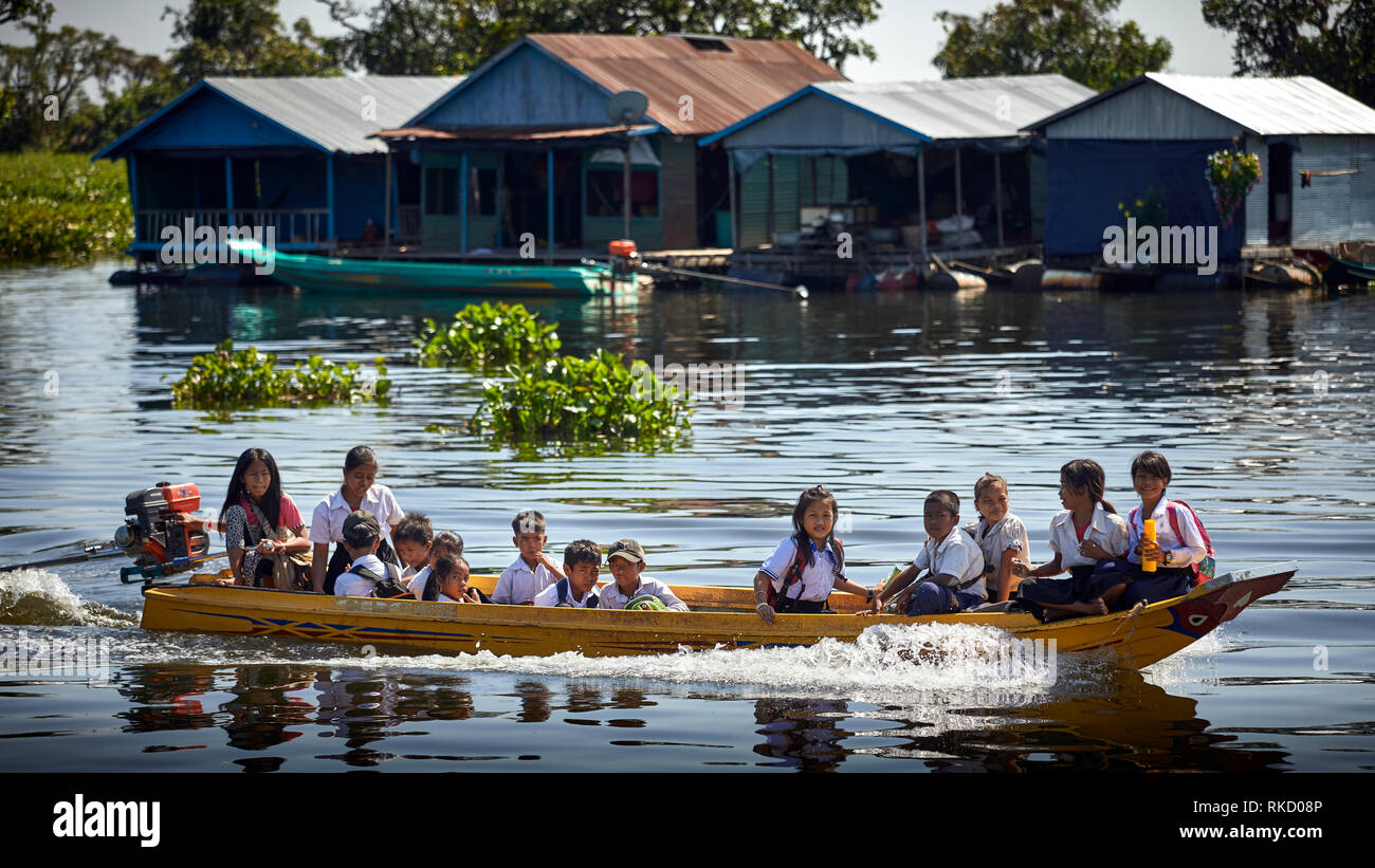 Tonlé Sap Lake,  Cambodia. 19th December, 2018. School children wearing uniforms in their floating village travel home from school in a motor boat. Ph - Stock Image