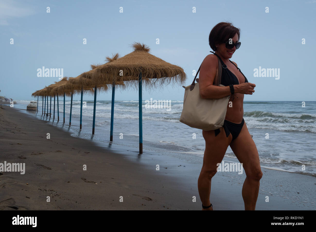 Woman in bikini walking past beach umbrellas as the tide water is coming in - Stock Image