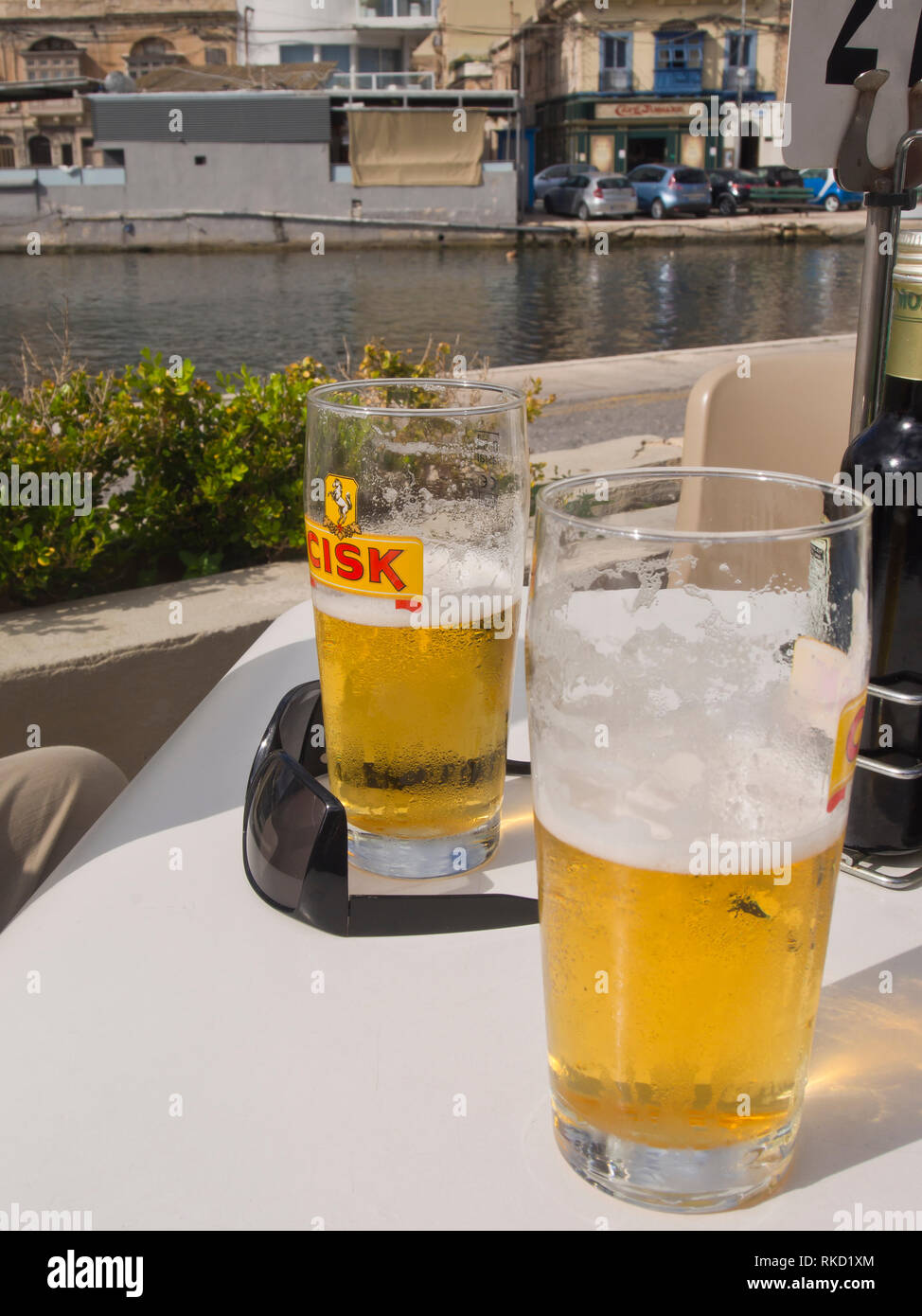 Half full - or empty glasses of Cisk beer on an outdoors table in the sun, holiday in Malta near Valetta Stock Photo