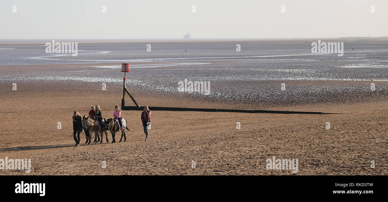 Children riding donkeys on Cleethorpes Beach - Stock Image