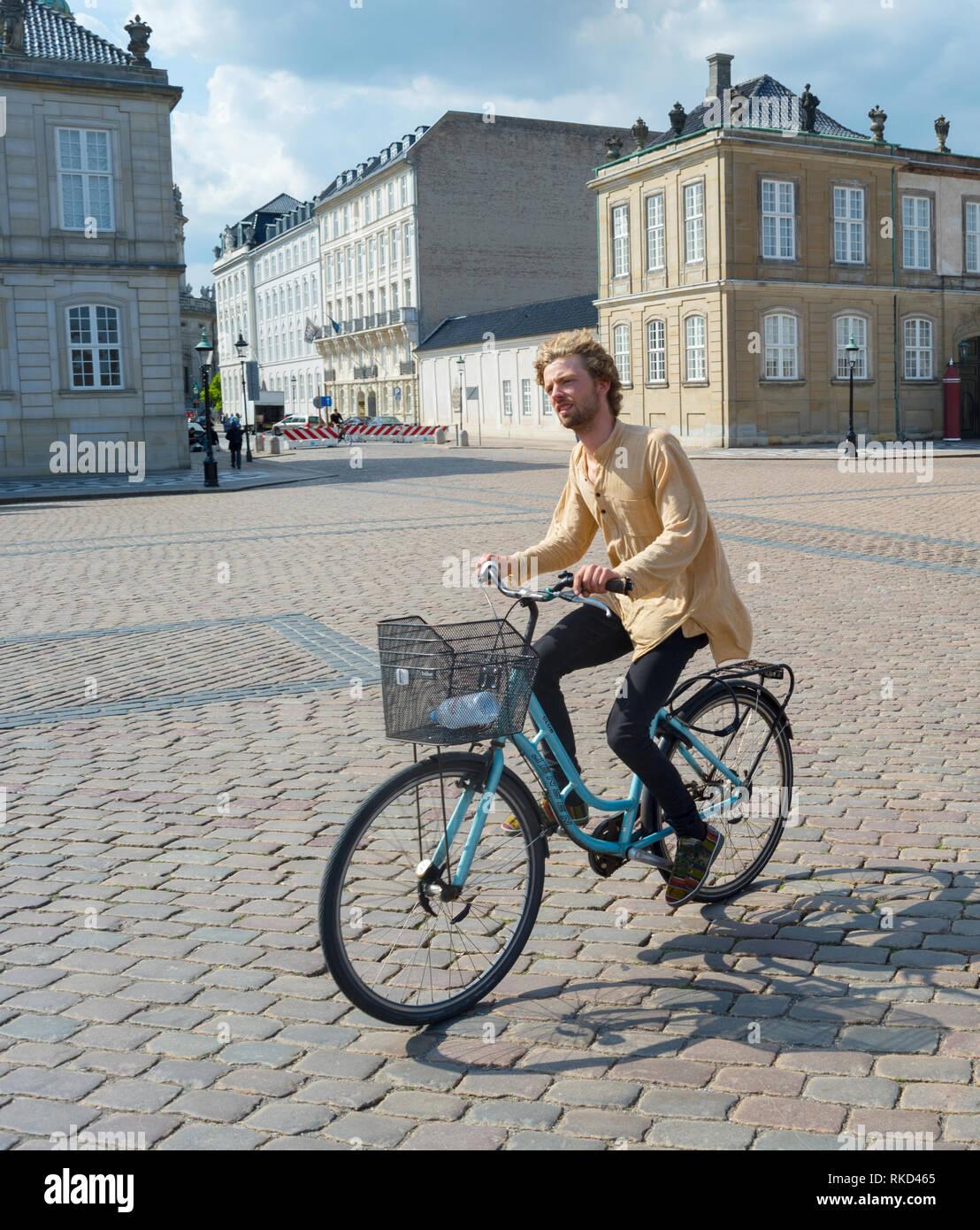 COPENHAGEN, DENMARK - JUNE 14, 2019:  Young hipster man riding city bicycle in bright sunshine at Amalienborg Palace Square, Copenhagen, Denmark, Euro Stock Photo