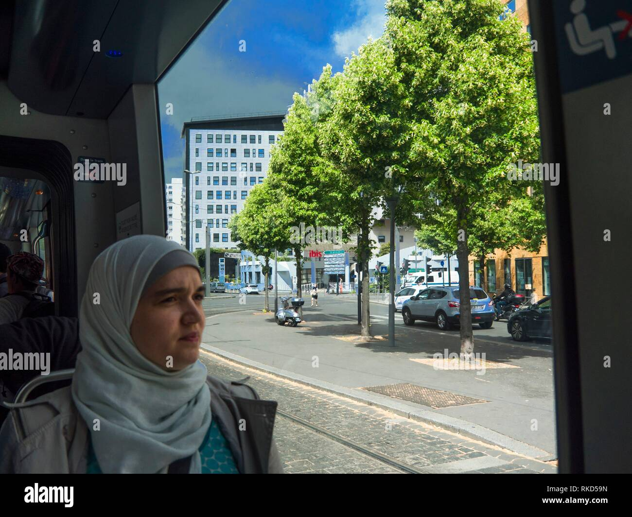 France, Nouvelle Aquitaine, Gironde. Woman with a ´Hijab´ in a tram at Bordeaux. A hijab is a veil traditionally worn by Muslim women in the presence - Stock Image