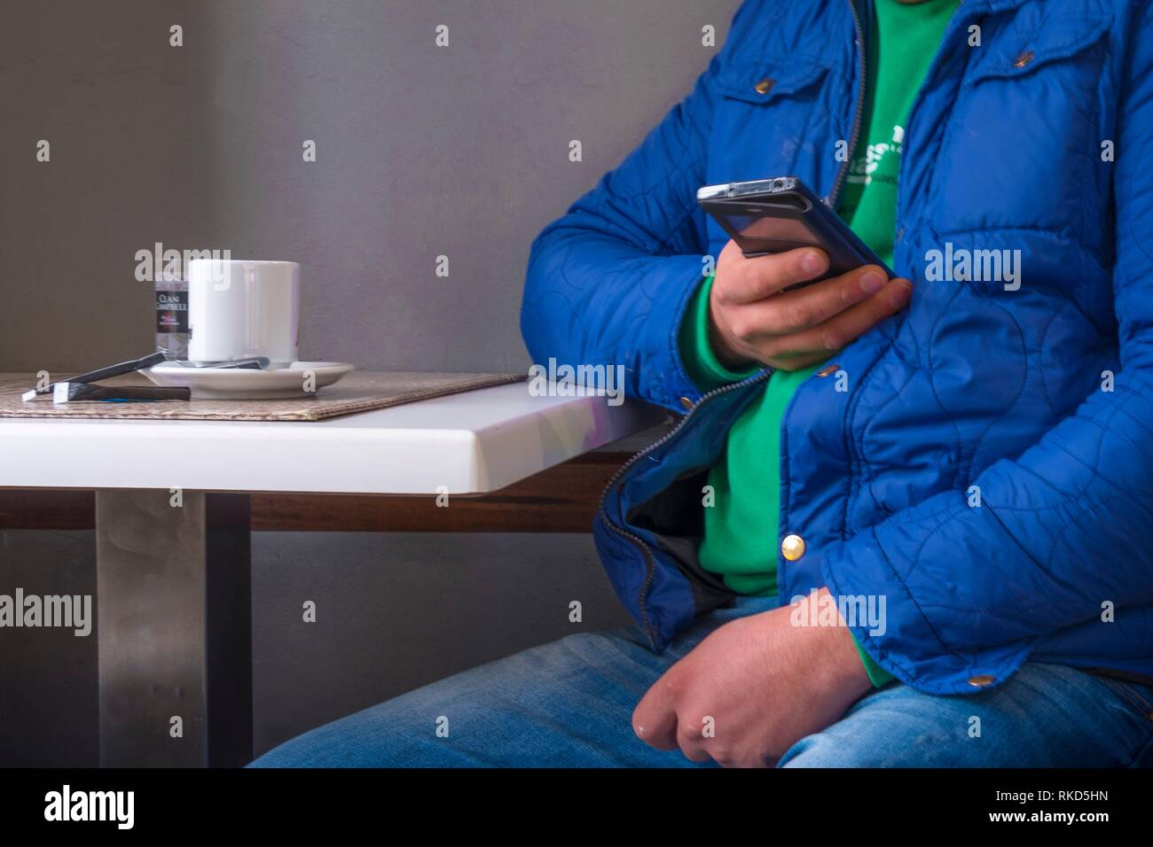 Man in cafe, using cell phone. France - Stock Image