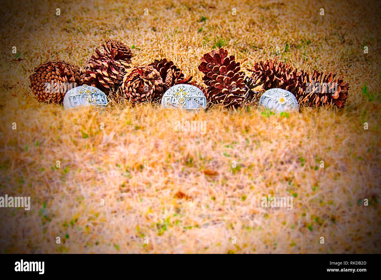 Close-up of several pinecones on the ground with three handcrafted stones that have symbols on them and the words hope, faith and love. - Stock Image