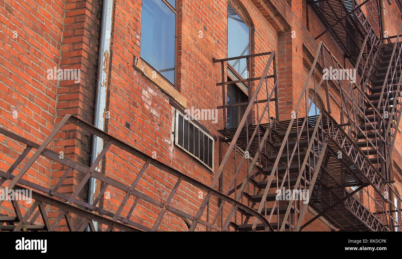 Brick faced industrial office  building with fire escape - Stock Image