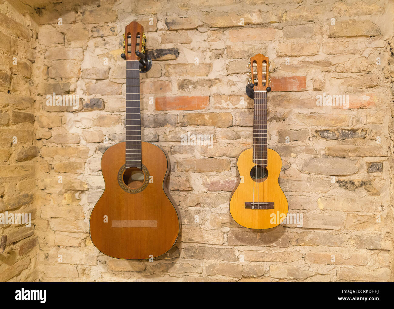 Two acoustic guitars hanging on brick wall background indoors. Vintage retro style - Stock Image