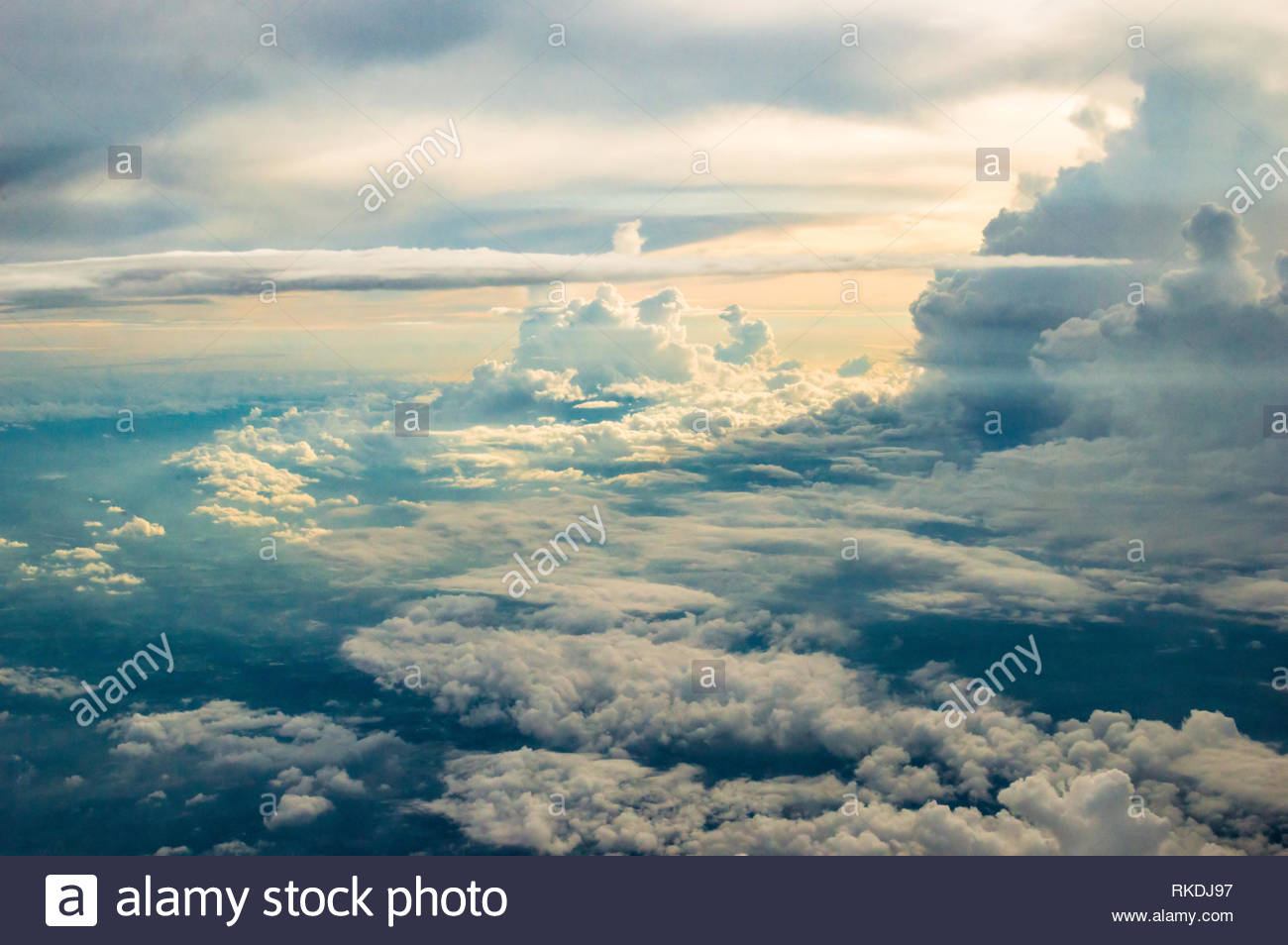 Dramatic cumulonimbus cloudscape after a rainy day, as photographed from a plane. Beautiful sunset sky. - Stock Image
