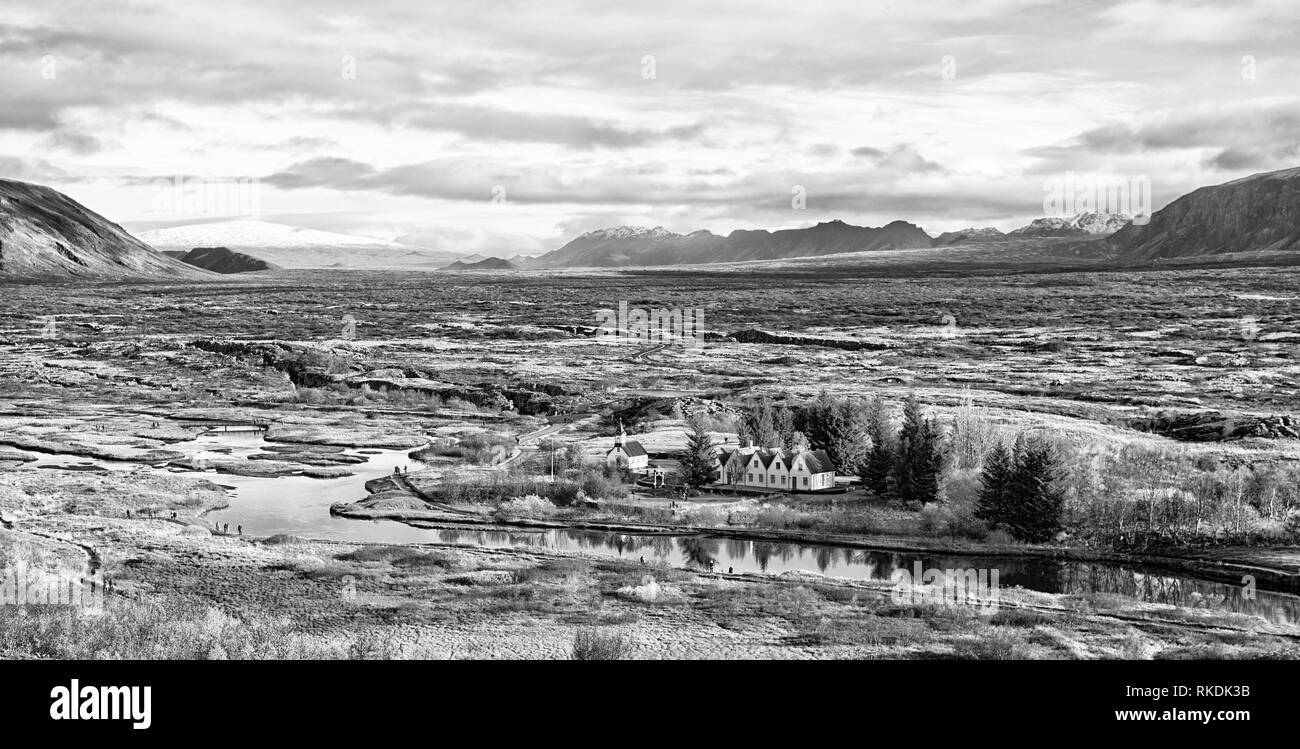 Haukadalur valley in Iceland. Little buildings in peaceful nature environment. Valley landscape sunny autumn day cloudy sky. Amazing beauty of valley. Beautiful landscape with river in valley. Stock Photo