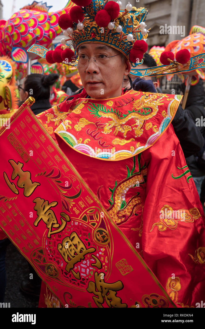 Chinese man wears a traditional Chinese dress and head during the Chinese New Year Parade in London, UK. - Stock Image