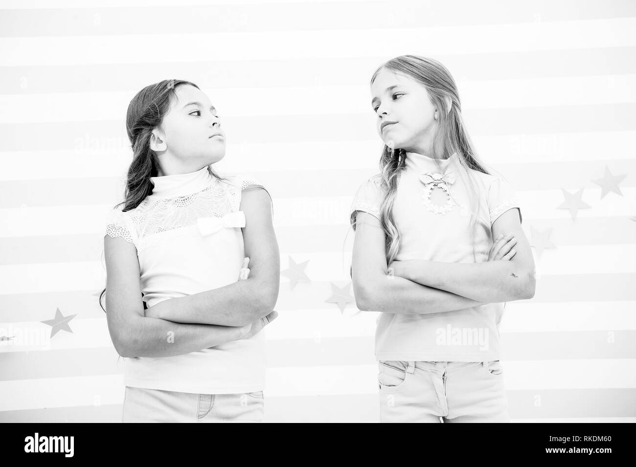 Schoolgirls haughty arrogant with folded arms chest. Best friends become enemies. Friendship relations issues. Girlish friendship problem. She definitely jealous. Girl arrogant faces confident pose. - Stock Image