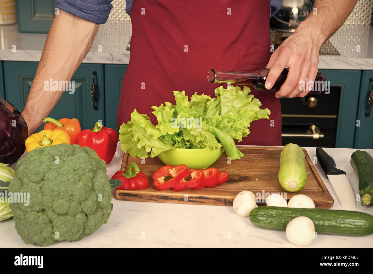Measure accurately. Nothing wrecks dish like a double portion of vinegar or oil. Hands of chef male pouring lettuce with vinegar or oil without measuring. Measuring issues can cause wasting products. - Stock Image