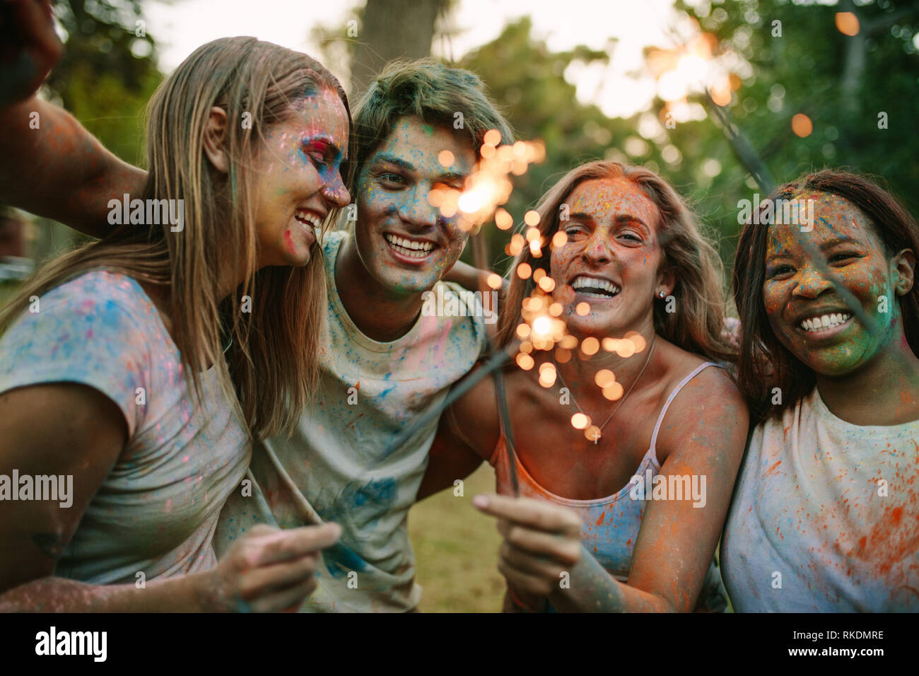 Friends having fun playing with fire sparkles while playing holi in a park. Friends enjoying holi with fire sparkles. - Stock Image