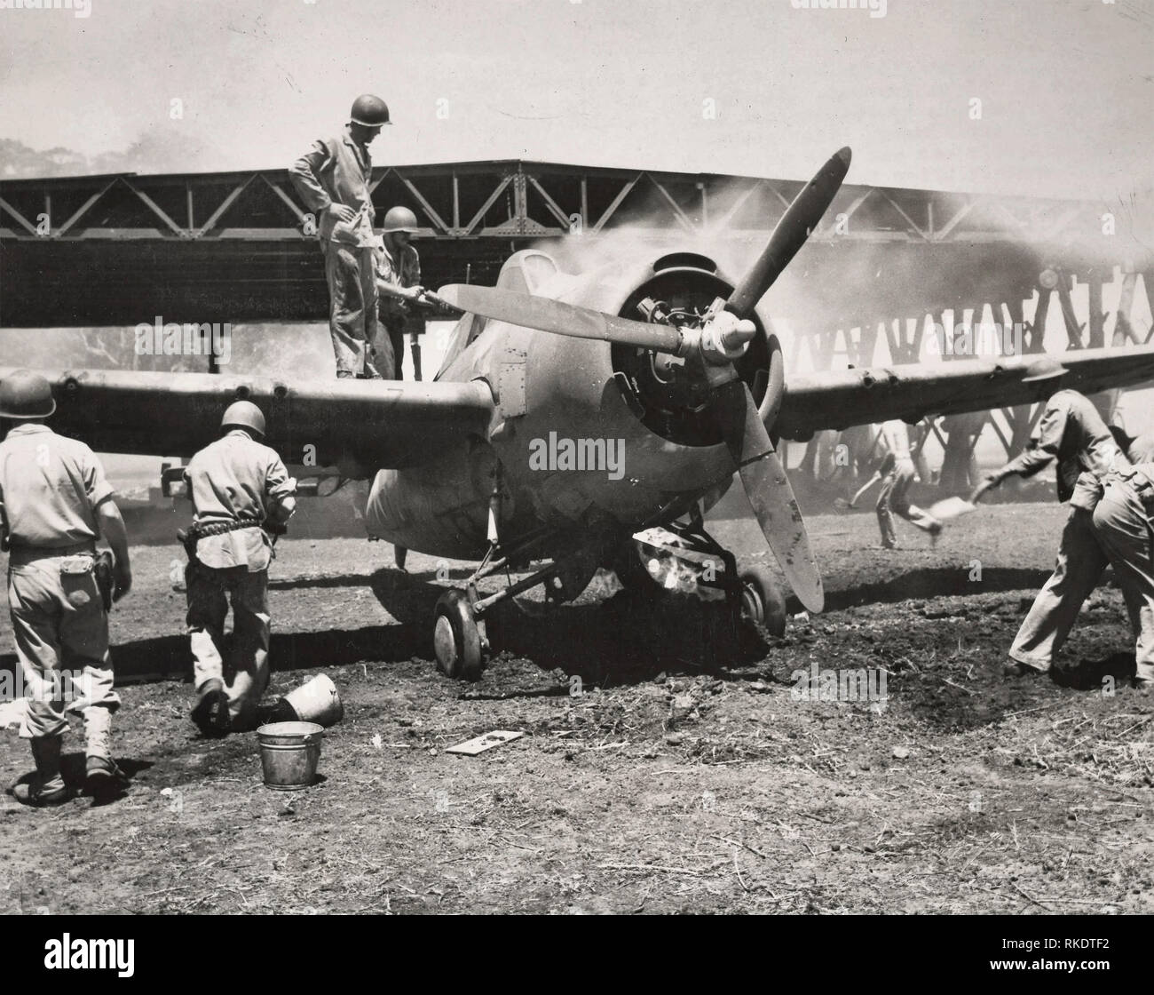 """Marine Fighter Plane Saved. Set afire by a Japanese bomb hit on the hanger in the background, this Marine fighter plan was pulled into the open by Leatherneck who used dirt and chemicals to extinguish the flames. The plane, a Grumman """"Wildcat"""" was NOT damaged seriously and was able to return to the air. The picture was taken shortly after the Marines captured a strategic Guadalcanal airport from the Japanese. 1942 - Stock Image"""