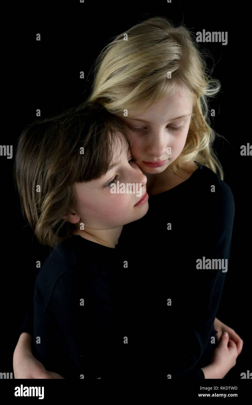 Two sisters in a solemn, loving embrace - Stock Image