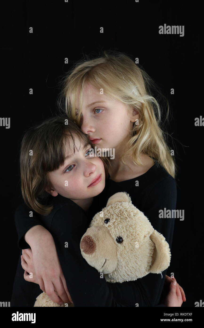 Two young sisters embracing each other in grief while holding teddy bear - Stock Image