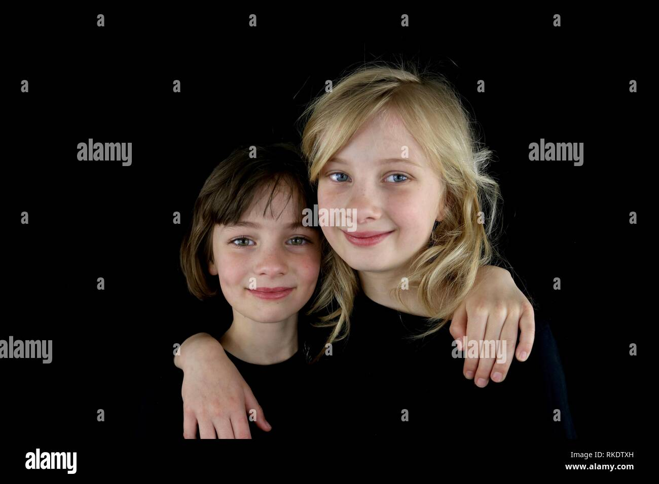 Two happy girls putting their arms around each other against a black background Stock Photo