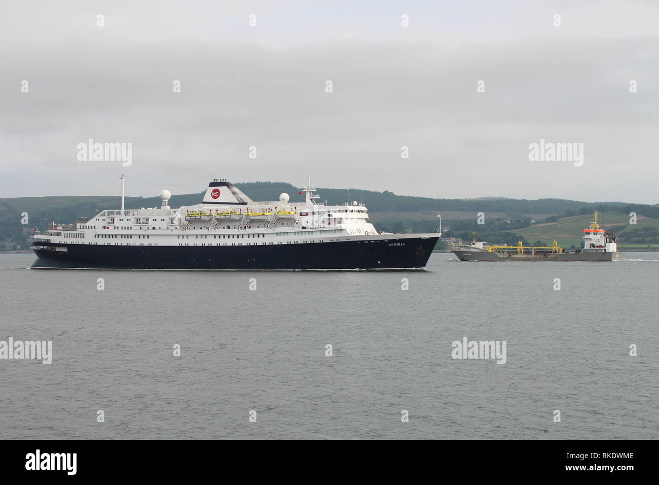 The cruise ship MV Astoria heads in to Greenock Ocean Terminal, as the dredger Freeway passes in the opposite direction. - Stock Image