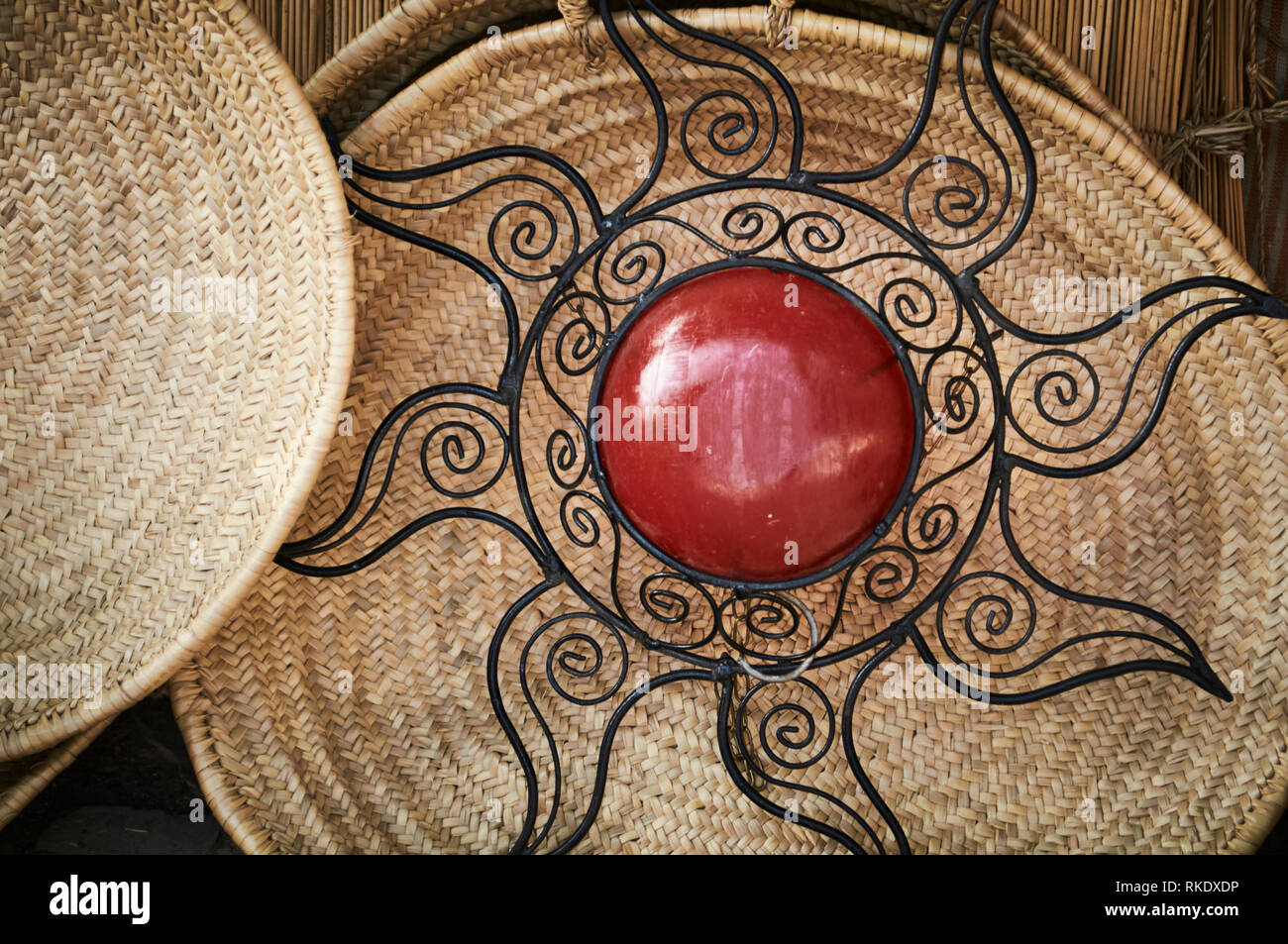 A decorative artwork, hand crafted metal welded sun with a red stone centre against wicker baskets and trays in a market in Chefchaouen, Morocco. - Stock Image