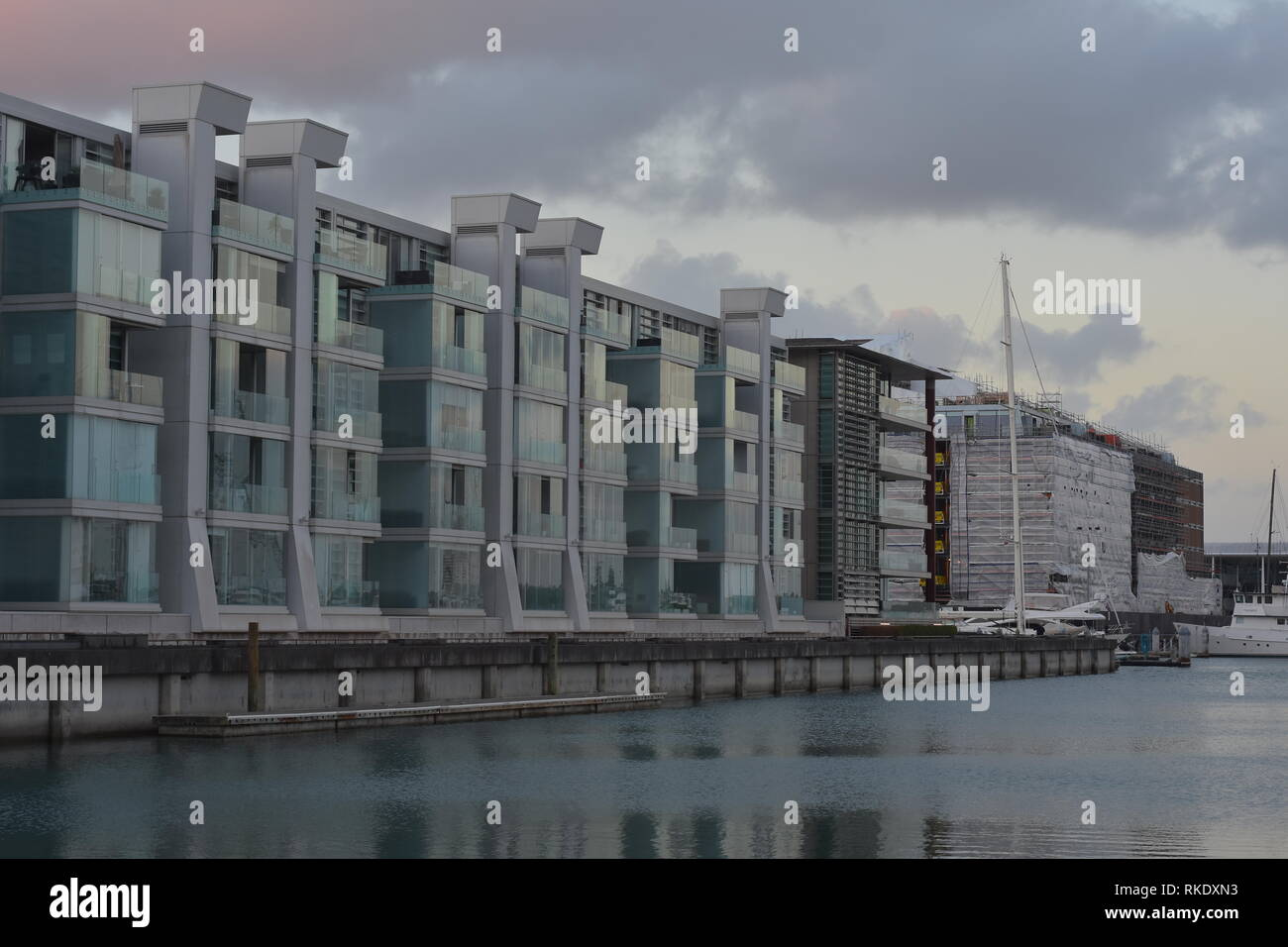 Modern apartments with large glass panels on exterior walls on waterfront of Auckland Viaduct Harbour in gray cloudy evening. - Stock Image